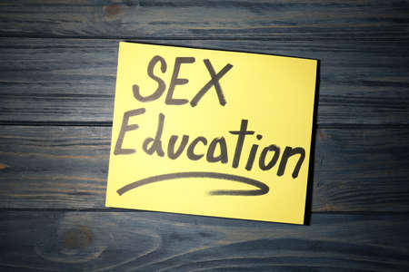 Note with phrase SEX EDUCATION on dark wooden background, top view