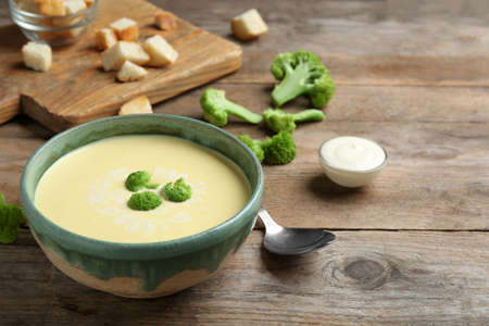 Bowl of cheese cream soup with broccoli served on wooden table, space for text