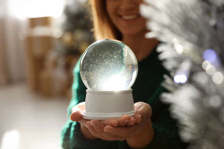 Happy woman at home, focus on hands with snow globe