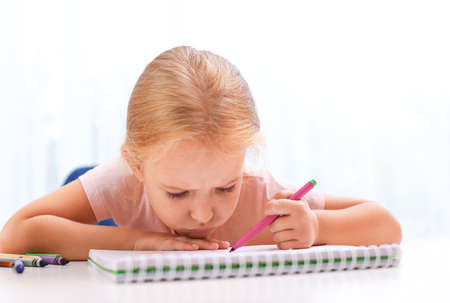 Upset little left-handed girl drawing at table in room 版權商用圖片