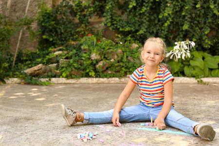 Cute little left-handed girl drawing with chalk on asphalt