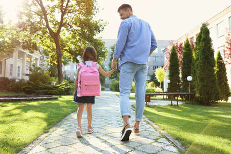 Father taking his little child to school through park