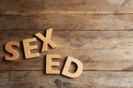 Phrase SEX ED made of different letters on wooden background, flat lay