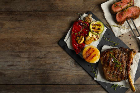Flat lay composition with grilled meat on wooden table. Space for text Reklamní fotografie