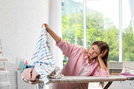 Tired girl holding unfolded laundry near ironing board at home