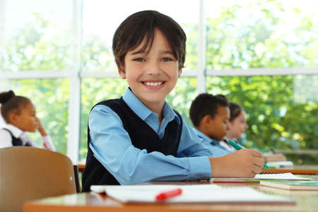 Boy wearing new school uniform in classroom