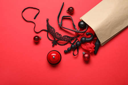 Paper bag with different toys and Christmas balls on red background, flat lay