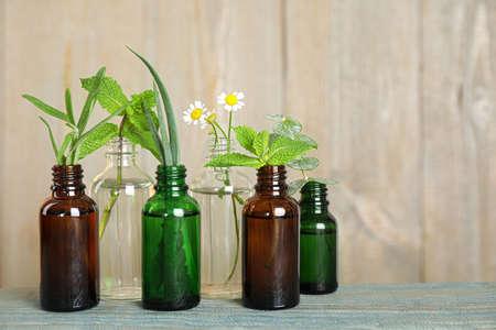 Bouteilles en verre de différentes huiles essentielles avec des plantes sur table