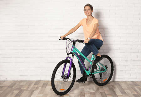 Happy young woman with bicycle near white brick wall indoors, space for text