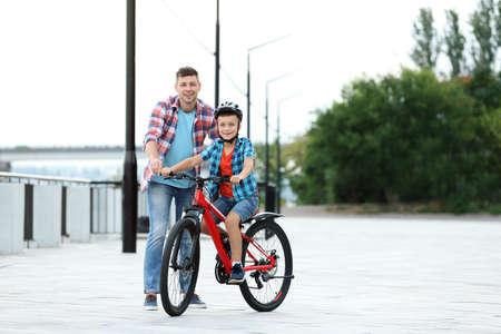 Dad teaching son to ride bicycle outdoors 版權商用圖片