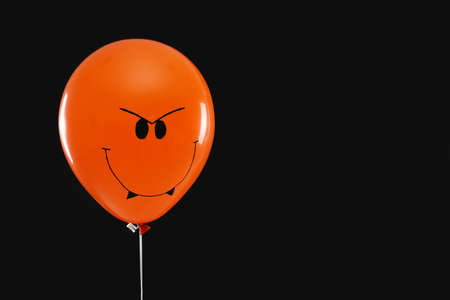 Spooky balloon for Halloween party on black background, space for text