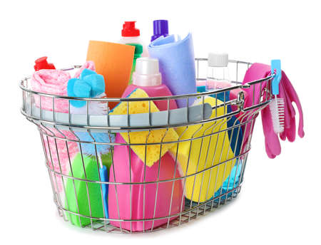 Metal shopping basket with different household chemicals on white background