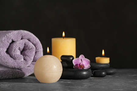 Composition with candles and spa stones on grey table