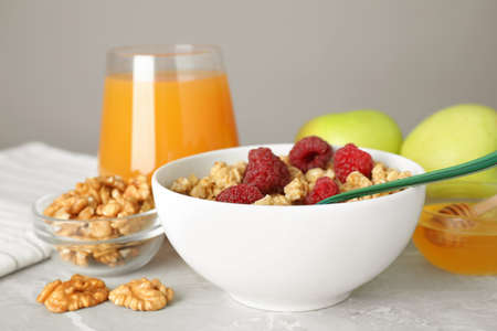 Healthy breakfast with granola and berries on light grey marble table, closeup