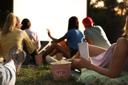 Giovani con popcorn e bevande che guardano film in un cinema all'aperto, primo piano