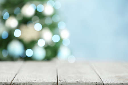 Empty white wooden table and blurred fir tree with Christmas lights on background, bokeh effect. Space for design