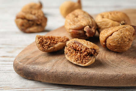 Wooden board with cut dried figs on white table, closeup