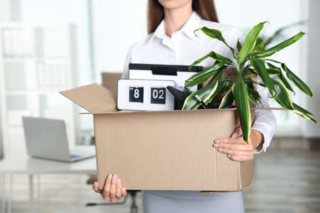 Young woman carrying box with stuff at office, closeup