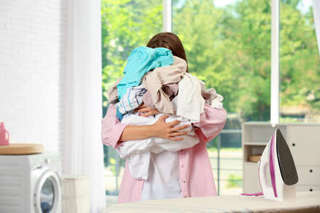 Girl holding clean laundry near ironing board at home