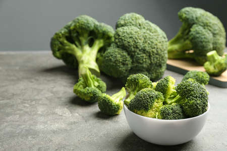 White bowl of fresh green broccoli on grey stone table, space for text