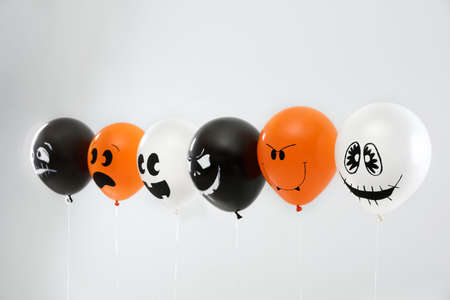 Spooky balloons for Halloween party on light grey background
