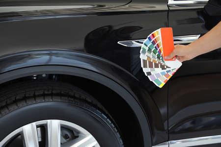 Young woman holding palette with color samples near black car, closeup Banco de Imagens
