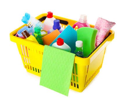 Yellow shopping basket with different household chemicals on white background
