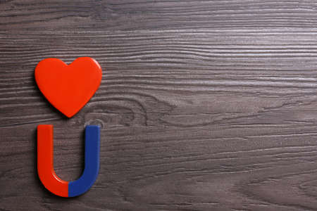 Red and blue horseshoe magnet with decorative heart on dark grey wooden background, flat lay. Space for text