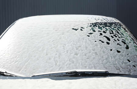 Automobile covered with foam at car wash, closeup of windshield