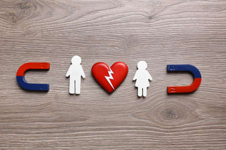 Magnets attracting paper couple on wooden background, flat lay. Love concept