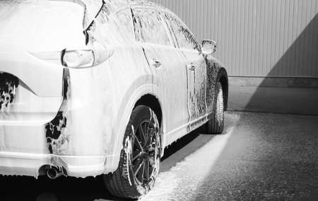 Luxury automobile covered with foam at car wash Stok Fotoğraf