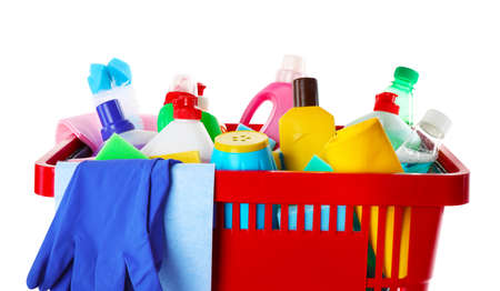 Shopping basket with different detergents, rag and gloves on white background