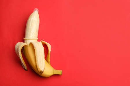 Banana with condom and space for text on red background, top view. Safe sex