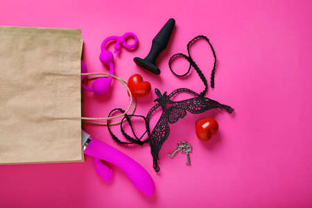 Paper shopping bag with different sex toys on pink background, flat lay