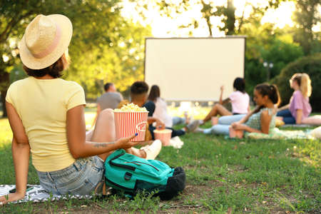Young woman with popcorn watching movie in open air cinema. Space for text