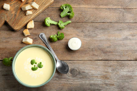 Flat lay composition with bowl of cheese cream soup and broccoli on wooden table, space for text