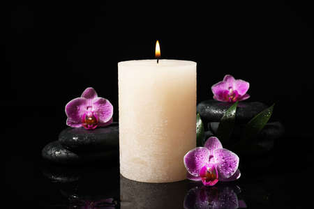 Composition with candle and spa stones on black background