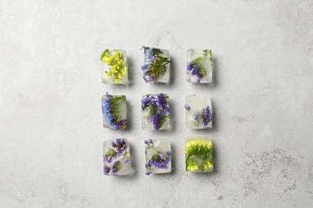 Ice cubes with flowers on light stone background, flat lay Stock Photo