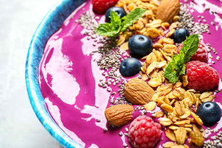 Delicious acai smoothie with granola and berries in dessert bowl on table, closeup Reklamní fotografie