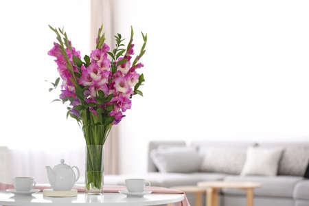 Vase with beautiful pink gladiolus flowers on wooden table in living room. Space for text Stock Photo