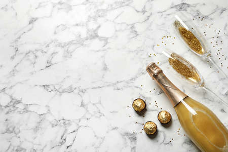 Flat lay composition with bottle of champagne for celebration on white marble background. Space for text Stock Photo