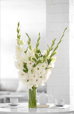 Vase with beautiful white gladiolus flowers on wooden table in living room