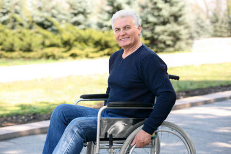 Senior man in wheelchair at park on sunny day