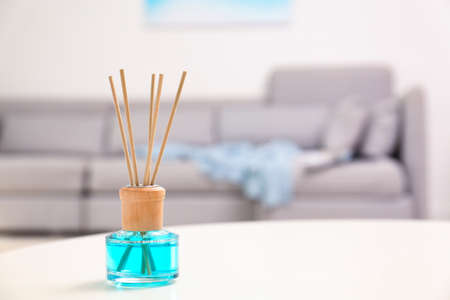 Reed air freshener with essential oil on table in room. Space for text