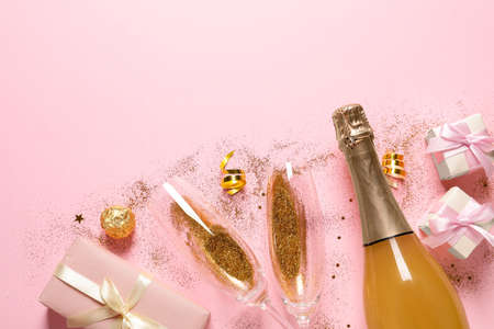 Flat lay composition with bottle of champagne for celebration on pink background. Space for text Stock Photo