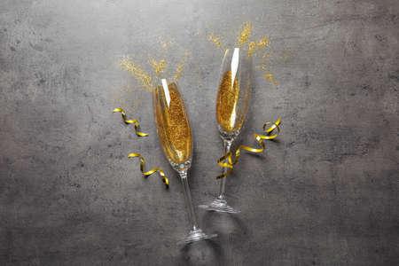 Flache Laienzusammensetzung mit Champagnergläsern zum Feiern auf grauem Steinhintergrund