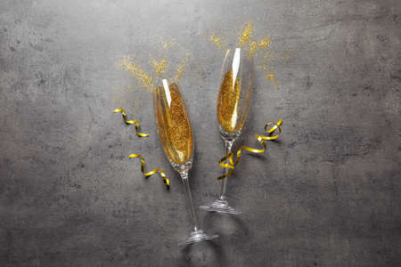 Flat lay composition with champagne glasses for celebration on grey stone background