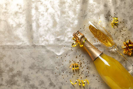 Flat lay composition with bottle of champagne for celebration on golden textile. Space for text Stock Photo
