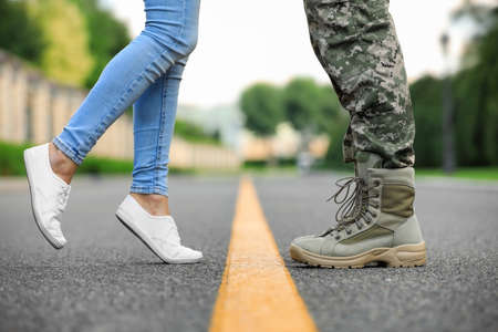 Man in military uniform and young woman separated by yellow line on road, closeup