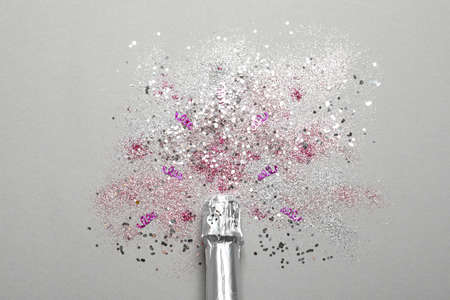 Bottle of champagne for celebration with glitter and confetti on grey background, top view Stock Photo